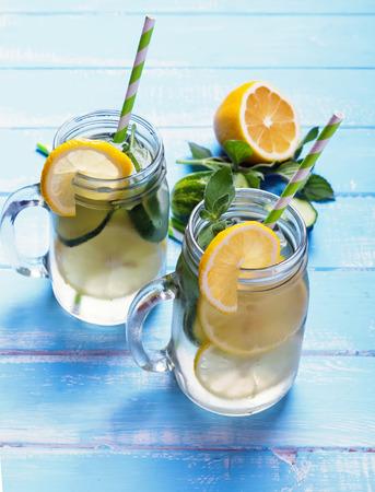 レモンとキュウリはガラス瓶に水をデトックスします。 写真素材