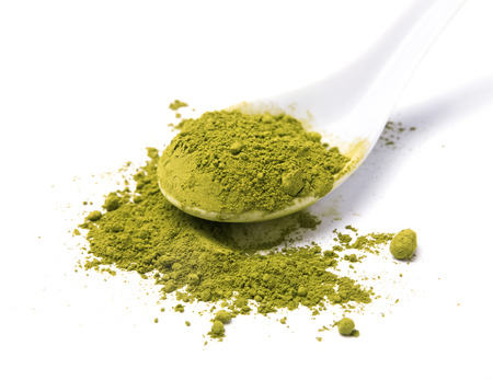 Matcha powder tea in a white spoon isolated on white background