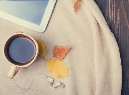 秋の朝の概念。一杯のコーヒー、タブレット、イヤホン、暖かい毛布、平面図。トーンの写真。 写真素材