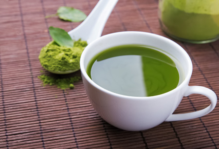 drinking tea: Green tea matcha in a white cup on the brown mat close-up