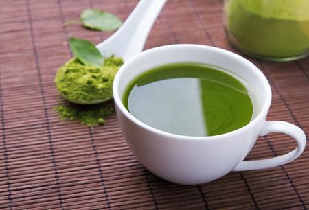 taza de te: Matcha t� verde en una taza blanca en la estera marr�n primer plano