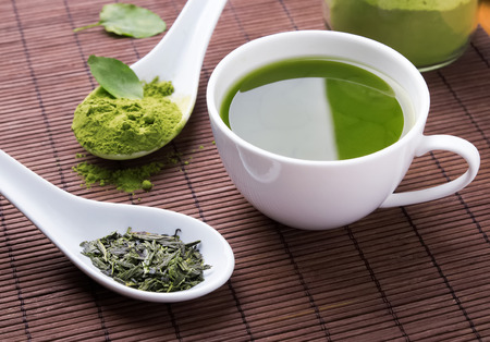 wooden spoon: Green tea on the brown mat close-up Stock Photo