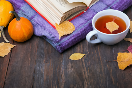 Autumn yellow leaves, pumpkins, tea, blanket and book on the wooden table