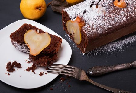 chocolate cakes: Chocolate cake with pears on the black background close-up Stock Photo