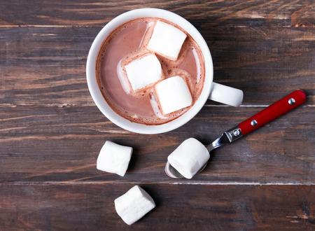 caliente: Taza de chocolate caliente con malvaviscos en la mesa de madera, vista desde arriba