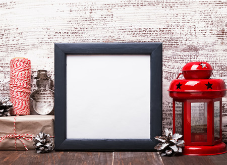 Blank frame, craft style Christmas decor and red lantern on the wooden table. Christmas mock-up.