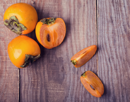 persimmons: Persimmons on the wooden table, top view. Toned photo. Stock Photo