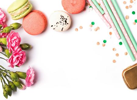 Macarons, pastel renkli kağıt çörek, beyaz zemin üzerine pembe çiçekler ve konfeti, üstten görünüm Stok Fotoğraf