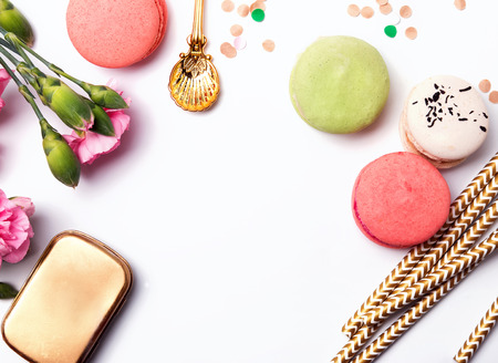 frippery: Flowers, paper straws, macarons and confetti on the white background, top view Stock Photo