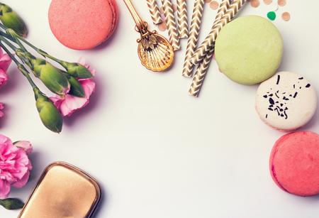 color in: Flores, macarons, paja de papel en colores pastel y caja de oro, vista desde arriba, retro tonos foto