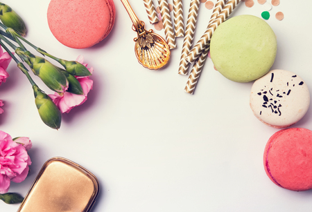 frippery: Flowers, macarons, paper straws in pastel color and golden box, top view, retro toned photo