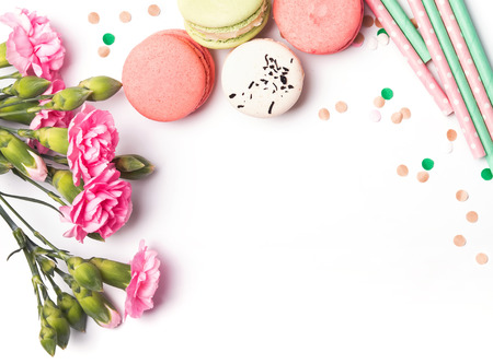 Flowers, macarons and paper straws in pastel color on the white background, top view