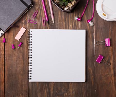空白のメモ帳と木製のテーブル トップ ビューにピンク色の文房具。モックアップを作成します。