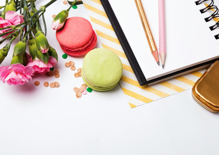 frippery: Flowers, macarons, paper notepad and pensils on white background