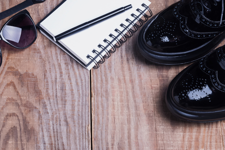 brogues: Stylish shoes, glasses and notepad on wooden table