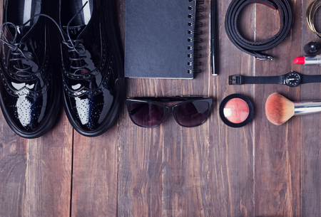 brogues: Women stylish outfit and make up on the wooden background, top view