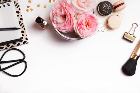 Vackra rosa blommor, franska makaroner, anteckningsblock och andra söta feminina grejer på vit bakgrund, ovanifrån