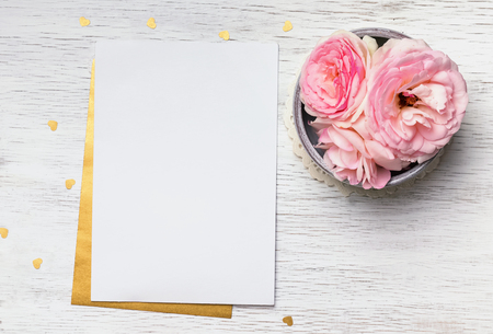 Blank paper and cute pink flowers on white wooden table, top view Imagens