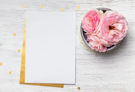 Blank Papier und niedliche rosa Blüten auf weißem Holztisch, Ansicht von oben