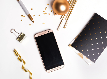 Cute golden decor and phone with empty screen, top view