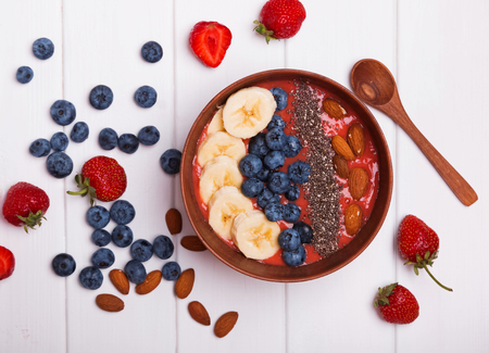 Strawberry smoothie bowl with berries amd chia seeds on white table, top view