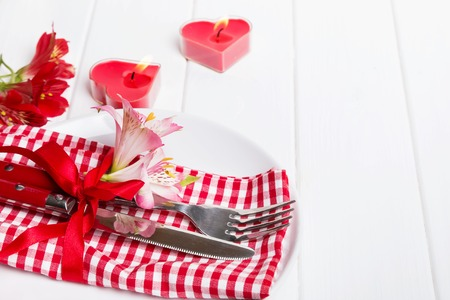 alstromeria: Valentines day table setting. Fork, knife with red ribbon and little flowers on the plate with red and white checkered serviette. Stock Photo