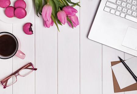 春のコンセプトです。ノート パソコン、コーヒー ピンクのチューリップとマカロンと女性の職場です。