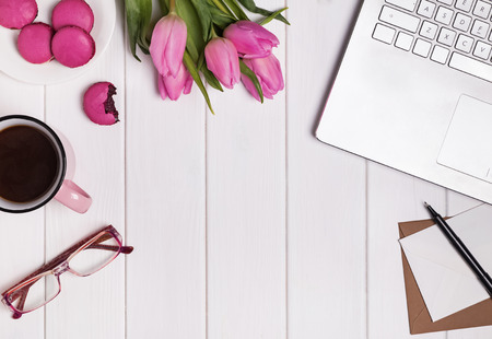 Spring concept. Womans workplace with laptop, coffee pink tulips and macarons. Stock Photo