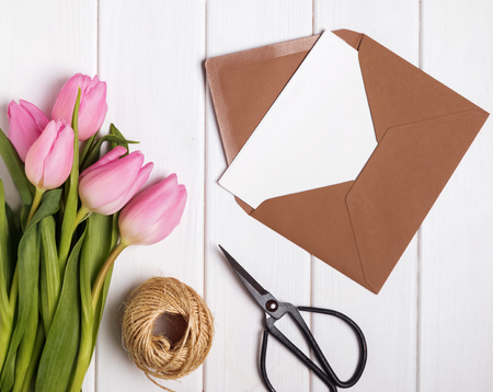 Pink tulips and envelope with blank papr on the white wooden tab