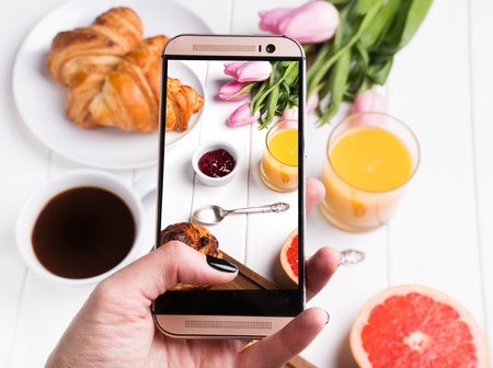 Womans hand taking photo of delicious breakfst with smartphone close-up