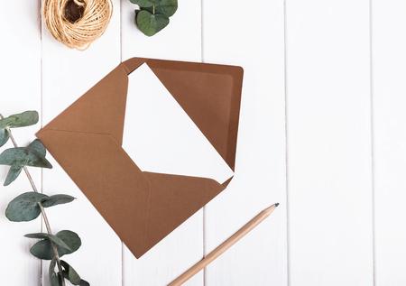 白いテーブルの上の空封筒、鉛筆、ユーカリ ブランチ