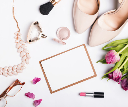 high view: Womans accessories of beige color, pink tulips and blank paper