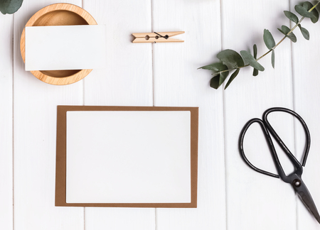 Blank card and paper on the wooden table with eucalyptus branches and simple objects
