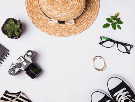 Straw hat, sneakers, vintage camera and other outfit on white background, top view 스톡 콘텐츠