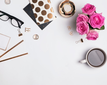 Woman's workplace with gold accessories, coffee and beautiful roses, top view Stockfoto