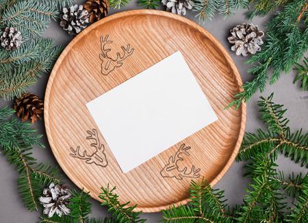 Blank christmas card template on wooden plate with fir branches blank christmas card template on wooden plate with fir branches top view stock photo maxwellsz