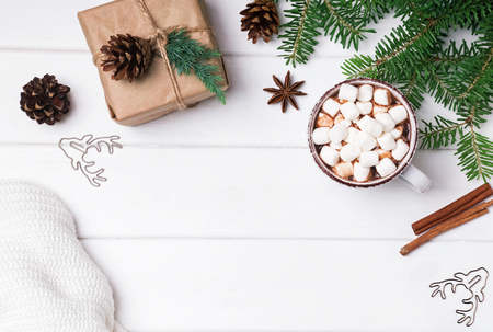 Hot cocoa, fir branches and knitted sweater on the white background, top view