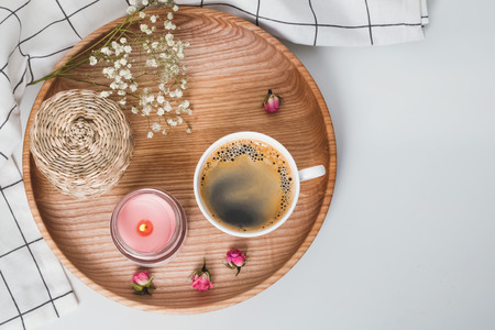 Cozy morning still life with coffee, candle and flowers on the wooden tray, top view