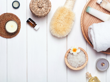 Spa essentials: sea salt, bottles, oils and dry brush, top view