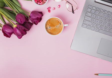 Femonine workplace concept. Laptop, coffee, glasses and purple tulips on the pink background