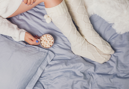 Womans legs in socks and hands holding cup of cocoa with marshmallows.