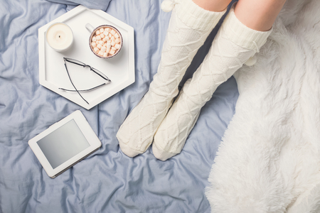 Womans legs in socks and cup of cocoa with marshmallows.