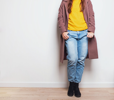 Autumn feminine fashion outfit in details. Woman wearing jeans and coat near the white wall.