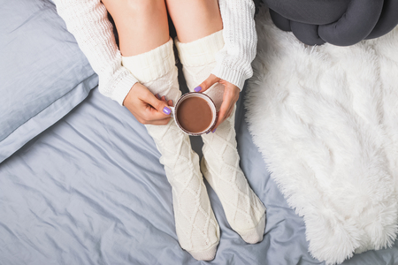 Womans legs in socks and hands holding cocoa or coffee. Autumn or winter concept. Morning in bed.