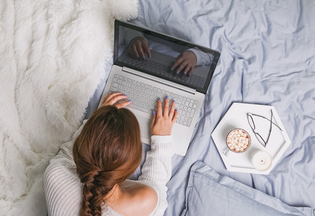 Young woman in white sweater lying on the bed and using laptop, top view.