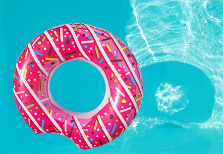Bright donut shape inflatable ring floating in the swimming pool with blue water, view from the top