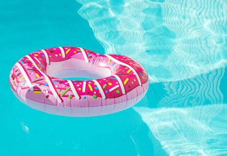 Bright donut shape inflatable ring floating in the swimming pool with blue water.