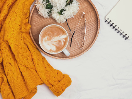 Coffee, flowers and yellow sweater on the white background
