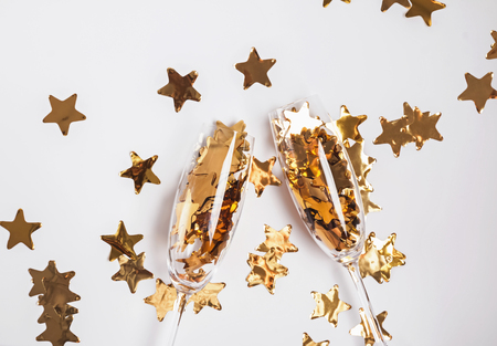Golden confetti in champagne glasses on the white background.