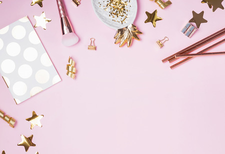 Golden decor and feminine accessories on the pink background,